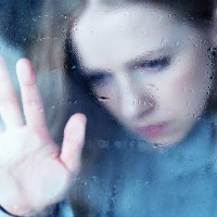 Melancholy girl at window