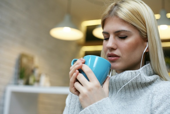 Female student listening to music on headphones with eyes closed and drinking coffee