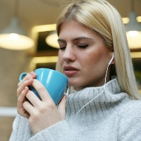 .Female student listening to music on headphones with eyes closed and drinking coffee.