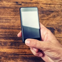 Male hand using smart phone over wooden office desk