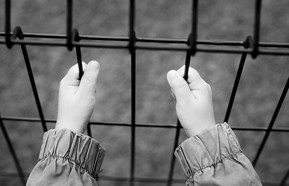 Child's hands holding a iron fence