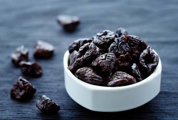 prunes in a bowl on a dark background. tinting. selective focus