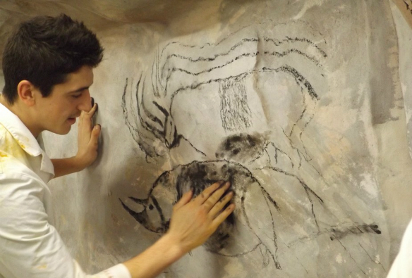 Third-year archaeology student Dominic Coe replicates a painting of rhino based on the original image in France's Grotte Chauvet.