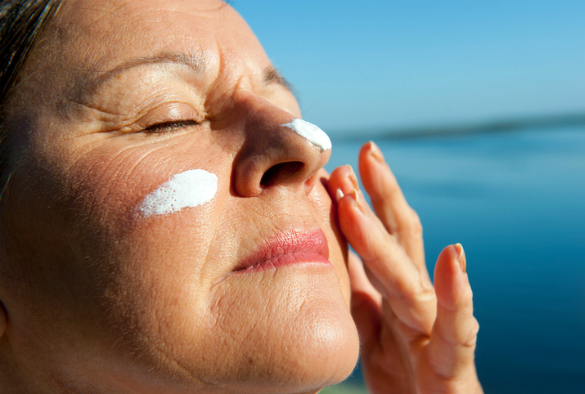 woman applying sun cream to face