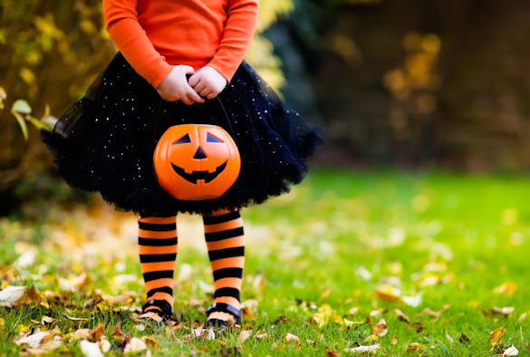Little girl holding a plastic pumpkin