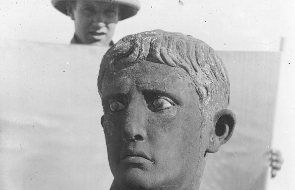 Professor John Garstang holds white background behind the Head of Augustus for photograph