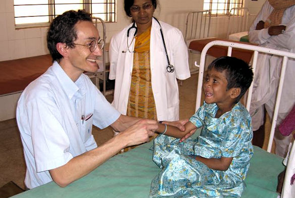 Professor Solomon examining a child who has recovered from a brain infection in Southern India