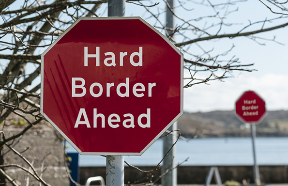 Sign at a stop junction in Ireland saying 'Hard Border Ahead'