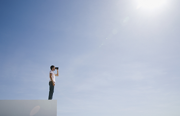 Man on pedestal with binoculars and blue sky outdoors