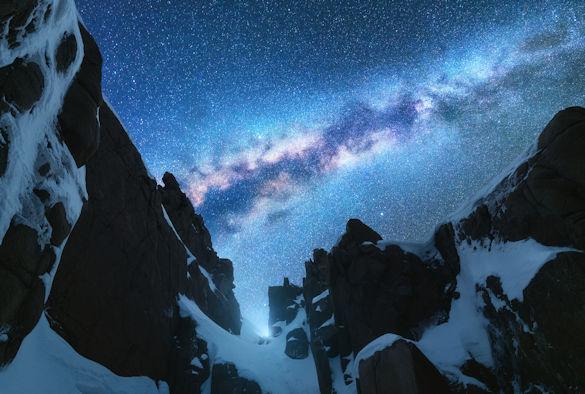 Milky way over snowy rocks