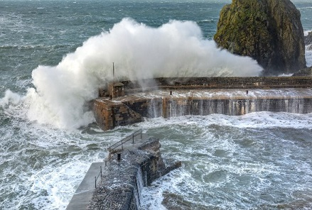 Waves washing over harbour wall