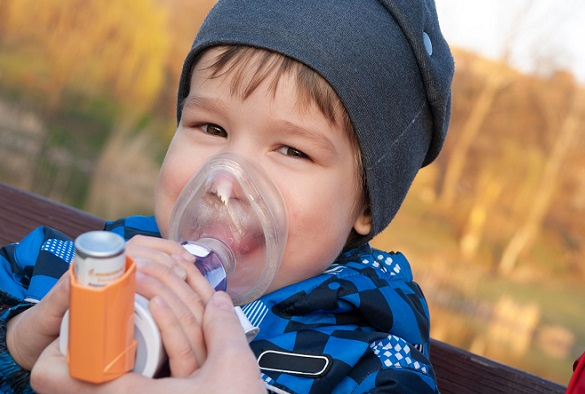 A small boy who suffering from illness bronchial asthma getting treatment with aerosol inhaler outdoors.