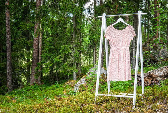 Organic clothes on hangers in forest