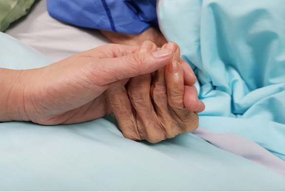 Carer holding hand of patient