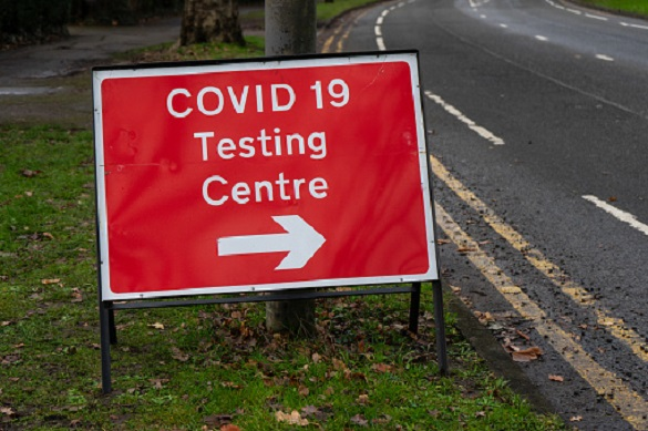 A red road sign directing people to a Coronavirus testing centre in the UK